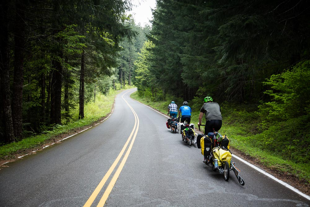Ben Horan, Mike Wolfe, and Phil Grove pedal down an Oregon road, skis in tow. PHOTO: Tom Robertson