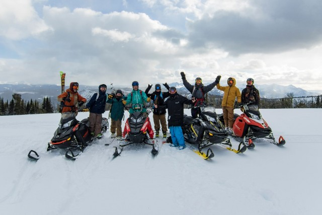 Skiers pose with snowmobiles Redbull Bracket Reel Competition