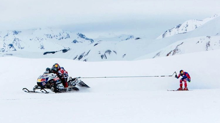 Ski racer gets towed by snowmobiler